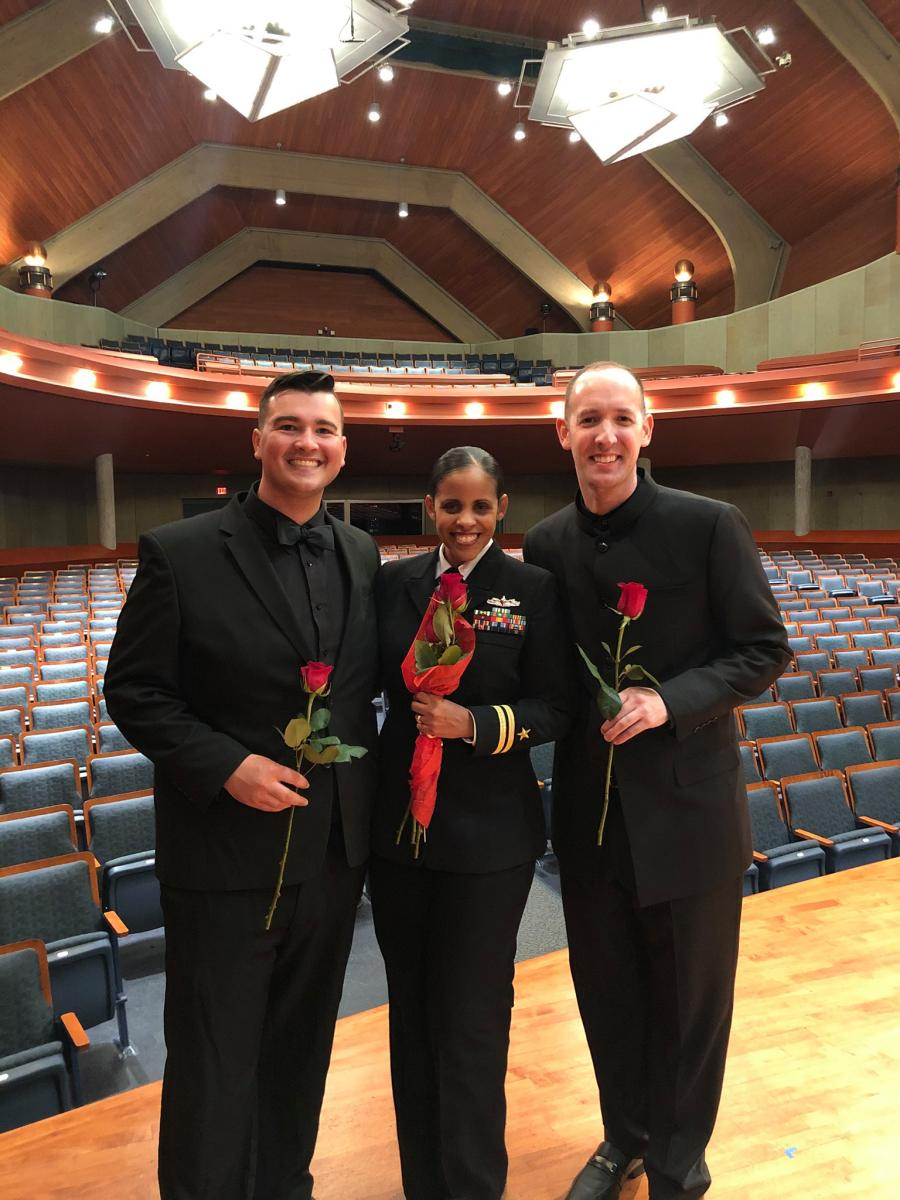 Three Graduate Conducting students standing on a stage carrying flowers post performance
